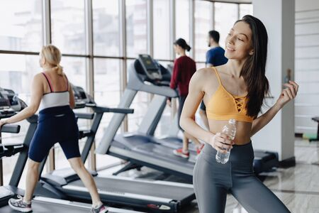 cozy young attractive girl in the gym drinking water on the background of treadmills Imagens - 135204259