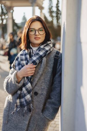 Attractive young girl wearing glasses in a coat on a urban background walking on a sunny day Imagens - 135204258