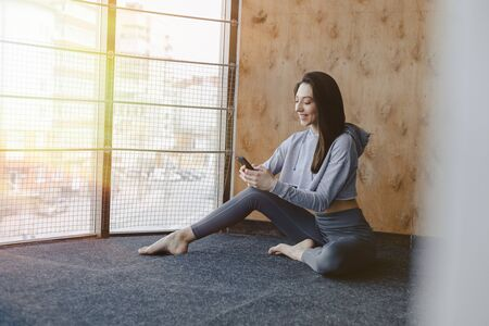 Young attractive fitness girl sitting on the floor near the window on the background of a wooden wall, resting on yoga classes at gym and talking on phone Imagens - 135204206