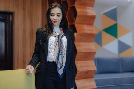 Young attractive emotional girl in a business style at a chair in a modern office or audience alone