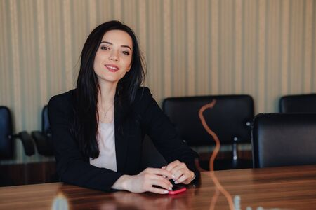 Young attractive emotional girl in business style clothes sitting at desk with phone in office or audience alone Imagens - 135204098