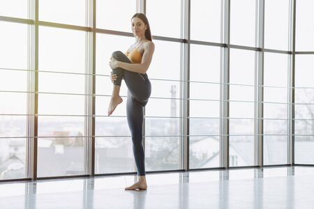 cozy young attractive girl doing fitness exercises with yoga on the floor against the background of panoramic windows Imagens - 135204204