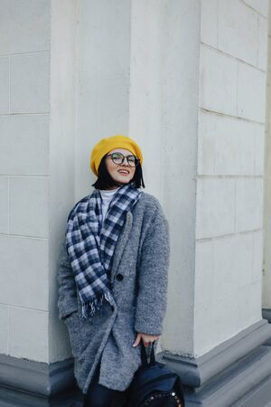 Attractive smiling young girl in stylish glasses in coat and yellow Beret on a simple light background