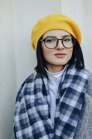 Attractive young girl in stylish glasses in coat and yellow Beret on a simple light background Imagens - 135204243