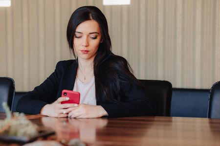 Young attractive emotional girl in business style clothes sitting at desk with phone in office or audience alone Imagens - 135204150
