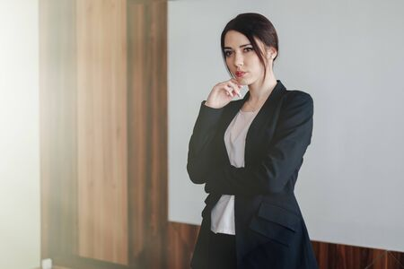 Young attractive emotional girl in business-style clothes on a plain white background in an office or audience alone Imagens - 135204143