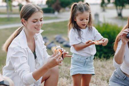 little girl having fun at picnic, eating pizza, drinks, summer and lawn Imagens - 135204315