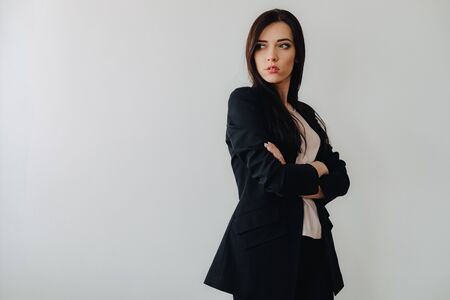 Young attractive emotional girl in business-style clothes on a plain white background in an office or audience alone Imagens