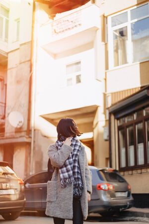 Attractive positive young girl wearing glasses in a coat on the background of buildings on cars on sunny day Imagens