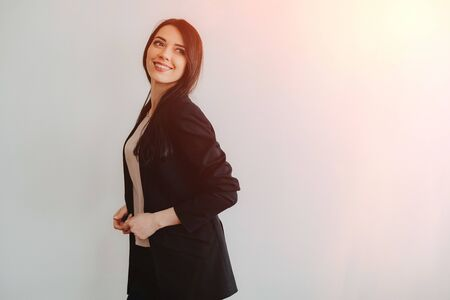 Young attractive emotional girl in business-style clothes on a plain white background in an office or audience alone Reklamní fotografie