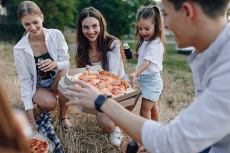 picnic friends with pizza and drinks, warm sunny day, sunset, company, fun, couples and mom with baby