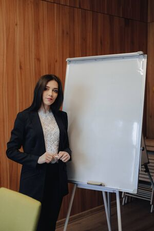 young emotional attractive girl in business-style clothes working with flipchart in a modern office or audience alone