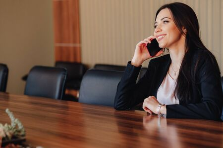 Young attractive emotional girl in business style clothes sitting at desk with phone in office or audience alone Imagens - 135204262