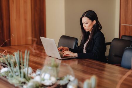 Young attractive emotional girl in business-style clothes sitting at a desk on a laptop and phone in the office or auditorium alone Imagens - 135204294