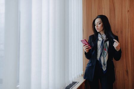 young emotional attractive girl in business-style clothes at a window with a telephone in a modern office or auditorium alone