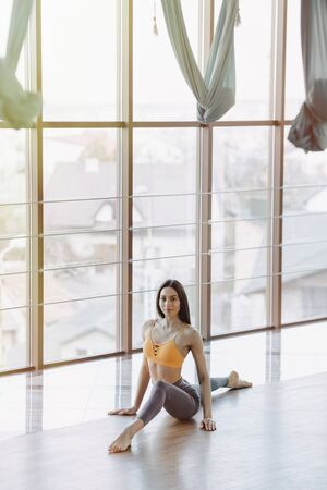 cozy young attractive girl doing fitness exercises with yoga on the floor against the background of panoramic windows Imagens - 135204303