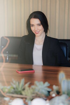 Young attractive emotional girl in business style clothes sitting at desk with phone in office or audience alone
