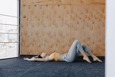 Young attractive fitness girl lying on the floor near the window on the background of a wooden wall, resting on yoga classes at gym Reklamní fotografie