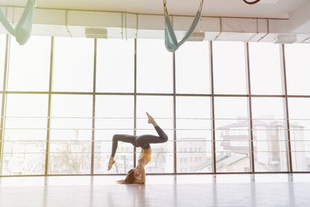 cozy young attractive girl doing fitness exercises with yoga on the floor against the background of panoramic windows Imagens - 135204320