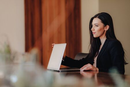 Young attractive emotional girl in business-style clothes sitting at a desk on a laptop and phone in the office or auditorium alone Imagens - 135204310