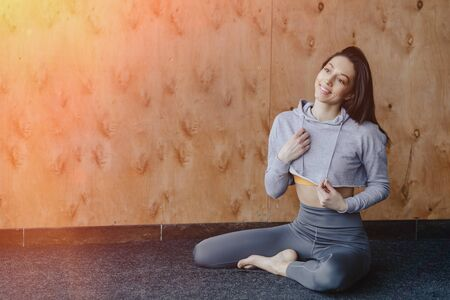 Young attractive fitness girl sitting on the floor near the window on the background of a wooden wall, resting on yoga classes at gym