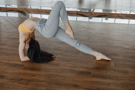 young attractive girl on a wooden floor doing yoga, stretching and relaxing with mirror on background