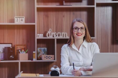 Cozy stylish woman works at a laptop desk in a modern office Imagens