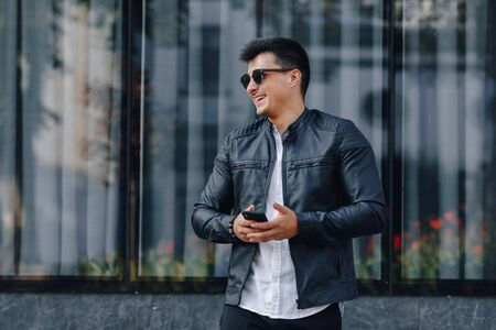 young stylish guy in glasses in black leather jacket with phone on simple glass background