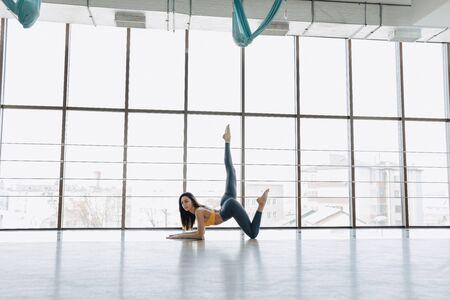 cozy young attractive girl doing fitness exercises with yoga on the floor against the background of panoramic windows Imagens - 136004789