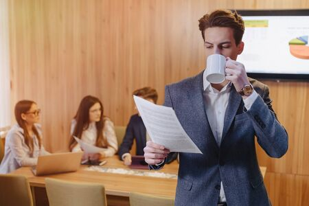 A stylish young man in a jacket and a shirt with a cup of coffee in his hand stands and reads documents on the background of working colleagues at office Imagens - 136205805
