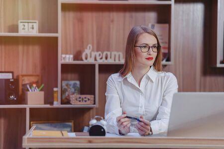 Cozy stylish woman works at a laptop desk in a modern office Reklamní fotografie