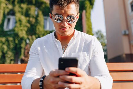 young stylish guy in white shirt with phone on bench on sunny warm day outdoors