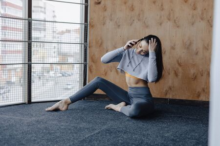 Young attractive fitness girl sitting on the floor near the window on the background of a wooden wall, resting on yoga classes at gym and talking on phone Imagens