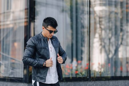 young stylish guy in glasses in black leather jacket on simple glass background