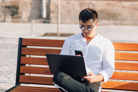 young stylish guy in white shirt with phone and notebook works on bench on sunny warm day outdoors, freelance