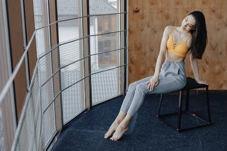 Young attractive fitness girl sitting on chair near the window on the background of a wooden wall, resting on yoga classes at gym Imagens