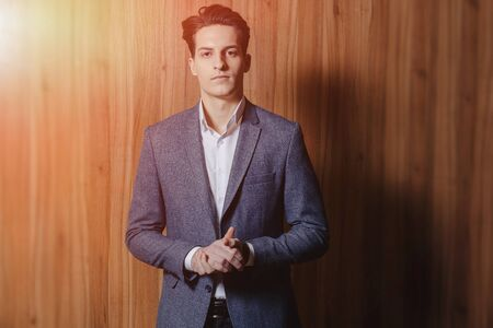 stylish guy in jacket at modern office on simple wooden background Imagens