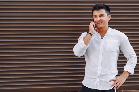 young stylish guy in shirt talking by phone on simple brown background