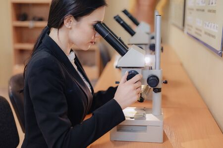 Young emotional attractive girl sitting at the table and working with a microscope in a modern office or audience alone Stock Photo
