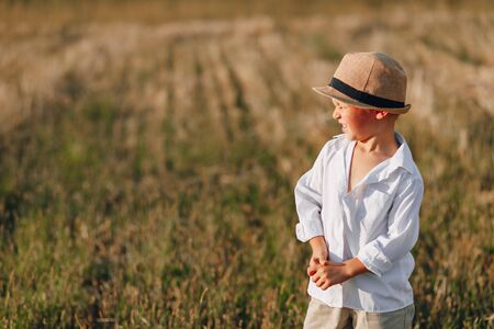 blond little boy in straw hat playing in field on mowed hay. summer, sunny weather, farming. happy childhood. sunny. 写真素材 - 143278288