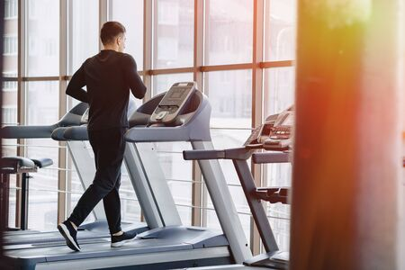 stylish guy in the gym is training on the treadmill. Healthy Lifestyle. wellness.