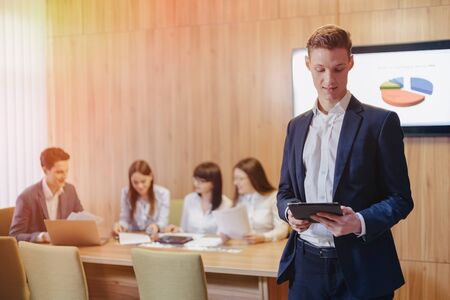 Stylish young businessman wearing a jacket and a shirt on the blurry background of a working office with people working with a tablet