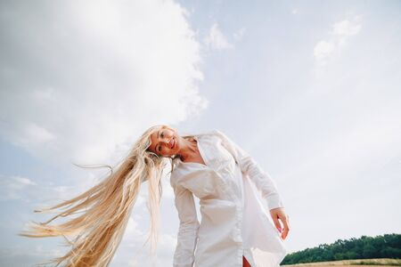 pretty woman with blond long hair in a field at sunset. summer, farming, nature and fresh air. sunny. Stockfoto