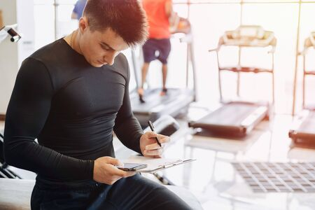 young guy trainer takes notes in the gym. personal trainer for sports. gym and sports.