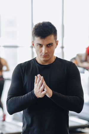 stylish guy in the gym rubs his hands with a talc. cloud of dust from hands. Healthy Lifestyle.