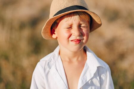 blond little boy in straw hat playing in field on mowed hay. summer, sunny weather, farming. happy childhood. sunny. Imagens