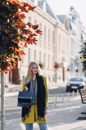 cute happy attractive blonde woman with packages on the street in sunny warm weather. shopping and positive emotions.