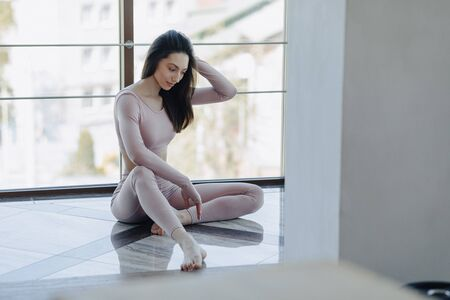 young attractive pretty girl in sportswear sitting on the floor by the window. nice sporty appearance and yoga.