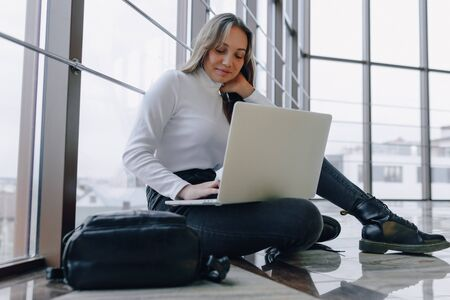 attractive girl working with laptop and things in airport terminal or office on floor. travel atmosphere or alternative work atmosphere. freelancer student travels to business meeting. concept of alternative workplace, technology and waiting. 스톡 콘텐츠