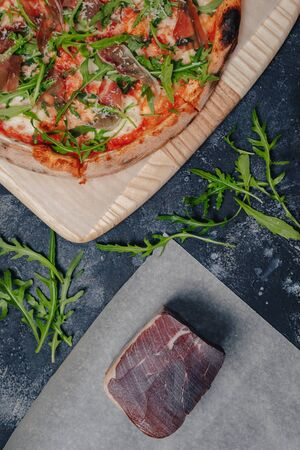 mouth-watering Neapolitan pizza on a blackboard with various delicious ingredients, free space for text